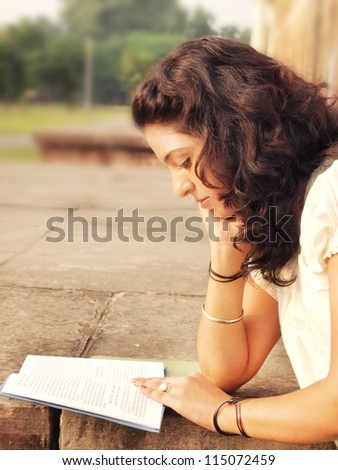 Portrait of an Asian / Indian college student reading book at campus. - stock photo