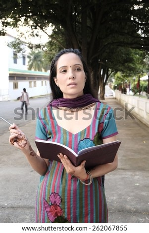 Portrait of an asian lecturer doing research outdoors. - stock photo