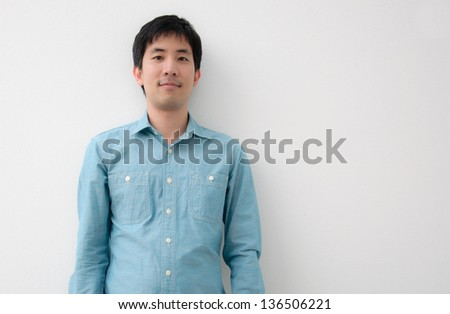 portrait of an asian man with white wall - stock photo