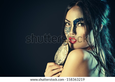 Portrait of an asian model with fantasy make-up. Black background.