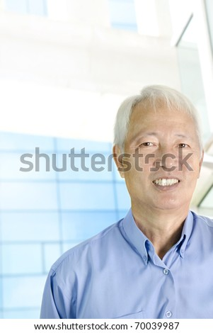 Portrait of an Asian  senior businessman standing in front modern building - stock photo