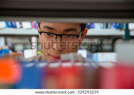 Portrait of an asian student searching book in library - stock photo