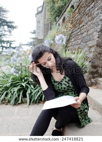 Portrait of an Asian teenager studying outdoor in campus. - stock photo