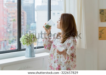 Portrait of an Asian woman drinking green smoothie in the morning