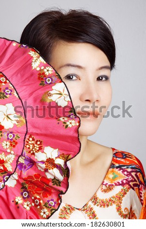 Portrait of an Asian woman with a fan - stock photo
