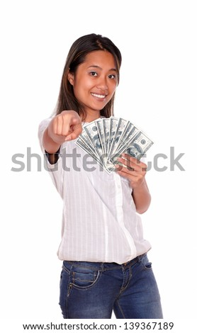 Portrait of an asiatic young woman pointing and looking at you with cash money against white background