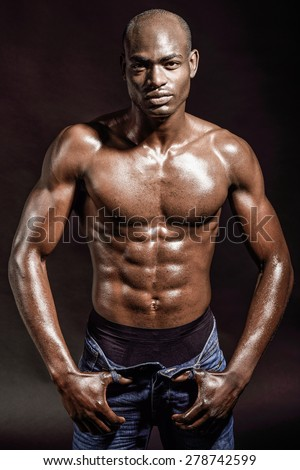 Portrait of an athletic black man on black background - stock photo
