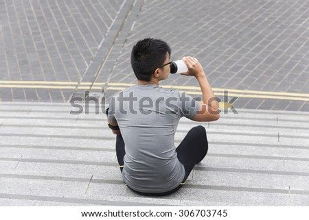 Portrait of an athletic Chinese man drinking during outdoors workout. Asian male runner taking break and drinking water. - stock photo