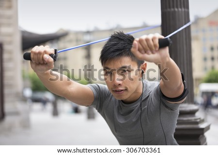 Portrait of an athletic Chinese man using stretch bands outdoors in urban setting. - stock photo