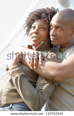 Portrait of an attractive african american couple hugging while visiting London with the London Eye and the sky in the background.
