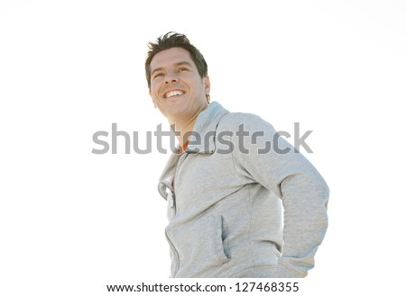 Portrait of an attractive and smiley sports man standing against a clean sky background during a sunny day. - stock photo