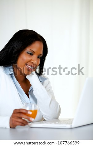 Portrait of an attractive and very relaxed young woman reading on laptop screen at soft composition - stock photo