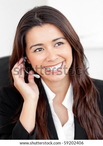 Portrait of an attractive asian businesswoman talking on phone with headphones sitting against white background - stock photo