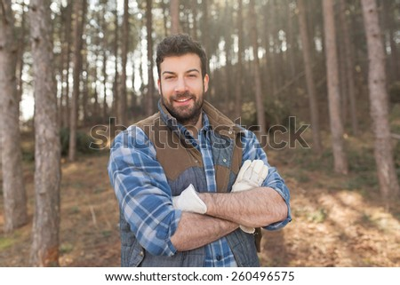 Portrait of an attractive bearded lumberjack man posing in the nature with his arms crossed, smiling and looking at the camera - stock photo