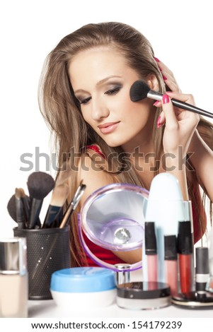 Portrait of an attractive, beauty young woman applying blusher