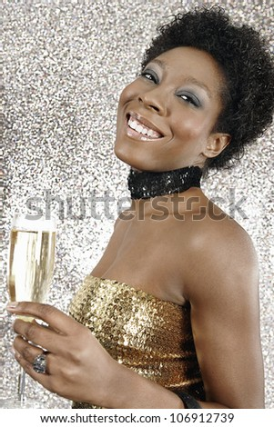 Portrait of an attractive black girl holding a glass of champagne on a silver glitter background, smiling. - stock photo