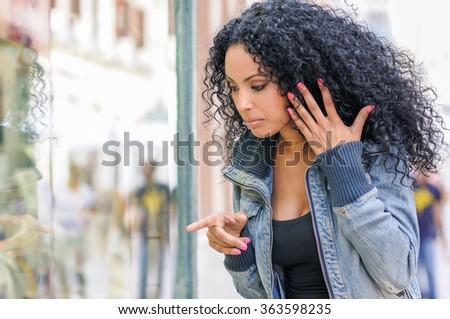 Portrait of an attractive black woman, afro hairstyle, looking at the shop window