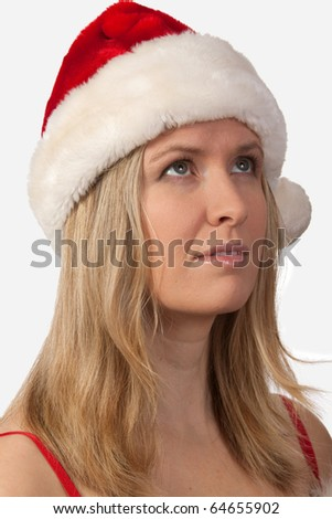 Portrait of an attractive blond woman wearing santa hat looking upwards - stock photo