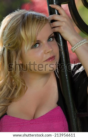 Portrait of an attractive blonde woman wearing pink and black. - stock photo