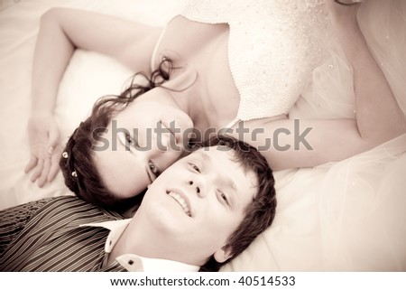 Portrait of an attractive bride and a groom which are lying on the bed