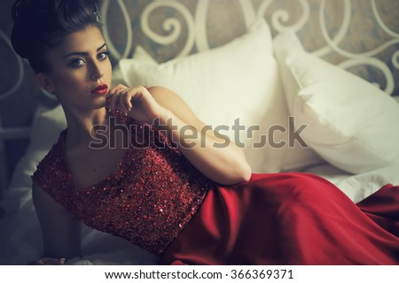 Portrait of an attractive brunette woman in an elegant red dress - stock photo