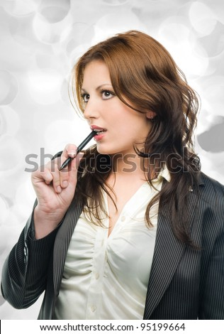 Portrait of an attractive business woman dreaming  on grey holiday lights - stock photo