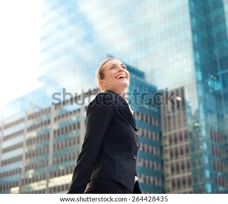 Portrait of an attractive business woman smiling and walking in the city - stock photo
