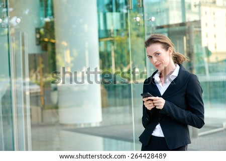 Portrait of an attractive business woman walking outside with mobile phone