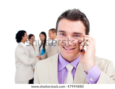Portrait of an attractive businessman on phone in front of his team - stock photo