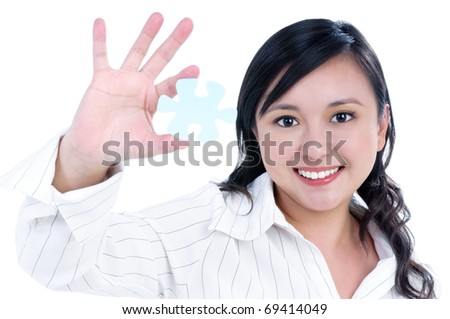 Portrait of an attractive businesswoman holding a piece of jigsaw puzzle over white background.