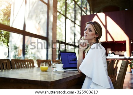 Portrait of an attractive businesswoman resting after on-line conference via laptop computer during her summer vacation, pretty Sweden female relaxing after working on net-book during coffee break  - stock photo