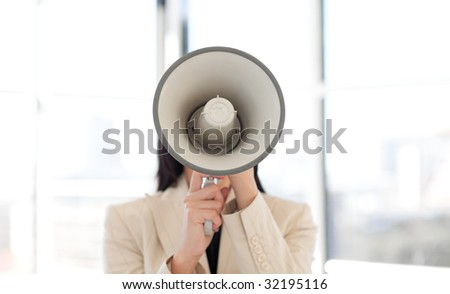 Portrait of an attractive businesswoman shouting through megaphone