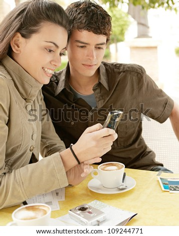 Portrait of an attractive couple writing postcards while sitting in a terrace coffee shop on holidays and using a smart phone together.