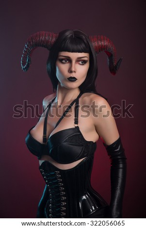 Portrait of an attractive demon girl in black corset and gloves, studio shot for Halloween   - stock photo