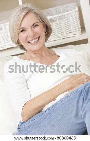 Portrait of an attractive elegant senior woman relaxing at home on a sofa. - stock photo