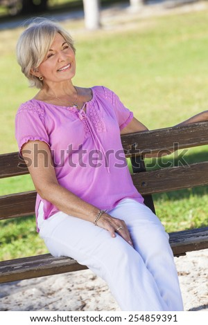 Portrait of an attractive elegant senior woman sitting outside with green grass behind her. - stock photo