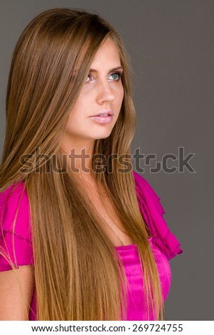 Portrait of an attractive fashionable young woman against gray background - stock photo