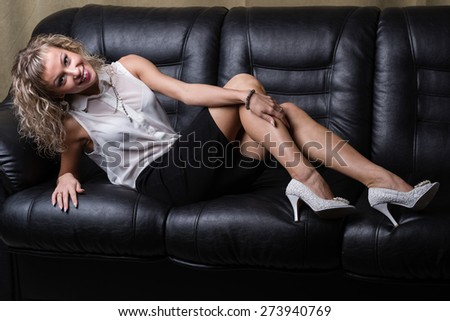 Portrait of an attractive fashionable young woman lying on the couch - stock photo
