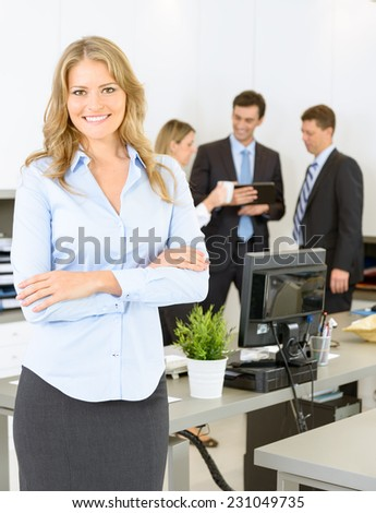 Portrait of an attractive female businesswoman with her colleagues in the background - stock photo