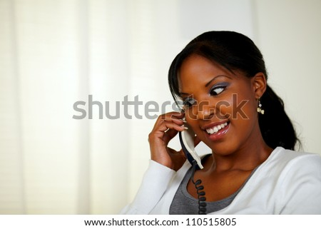 Portrait of an attractive female smiling and conversing on phone at soft colors composition
