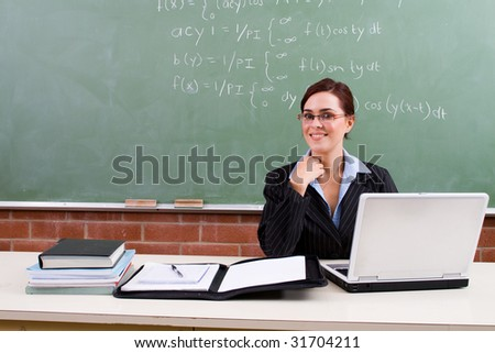 portrait of an attractive female teacher in classroom - stock photo