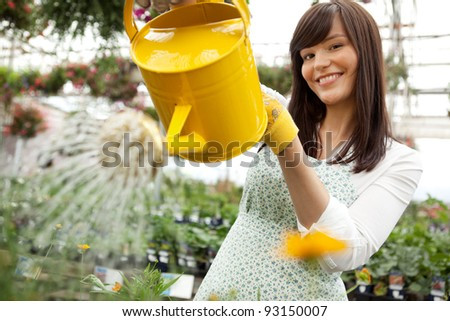 Portrait of an attractive female water plants with a watering can - stock photo