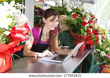 Portrait of an attractive florist business woman owner sitting at a flower shop counter using a laptop computer to place a stock order on line. Small business technology. - stock photo