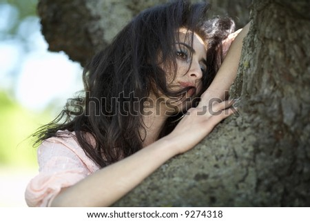 portrait of an attractive girl near a tree
