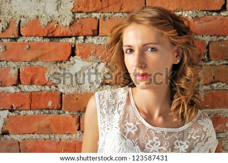 Portrait of an attractive girl next to a brick wall - stock photo