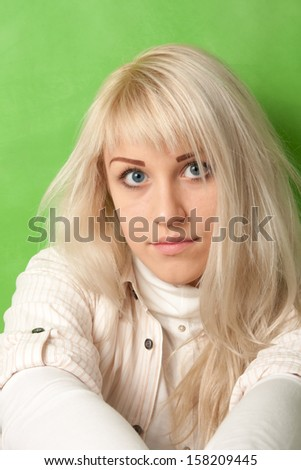 Portrait of an attractive girl on a bright green background - stock photo