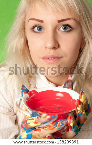Portrait of an attractive girl with colorful hands and a cup of red paint - stock photo