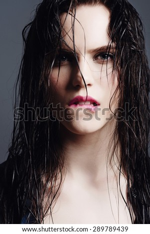 Portrait of an attractive girl with wet hair in studio on a blue background