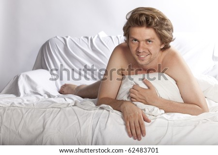 Portrait of an attractive happy young man hiding his nudity behind a pillow. Studio shot. See more in my portfolio - stock photo