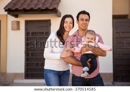 Portrait of an attractive Hispanic young couple and their baby girl standing in front of their new home and smiling - stock photo